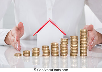 Close-up Of Businesswoman Protecting Coins And House Model