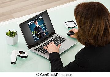 Businesswoman Reading Online Magazine On Laptop