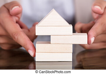 Businesswoman Removing Wooden Block From Model House