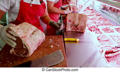 Close-up of butcher cutting quality porks in butcher shop. ...
