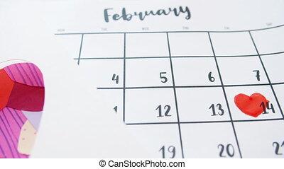 Close-up of calendar with heart shape around February 14 ...
