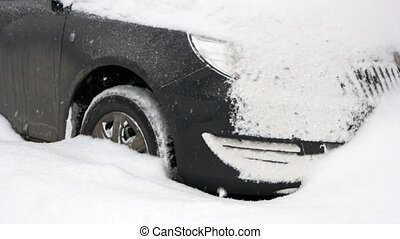 Close up of car stuck in snow drift. Black car covered with...