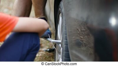Replace a broken tire with a special tool. Man changing tires on the car