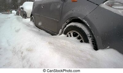 Close up of car wheels stuck in snow drift. Car covered with...