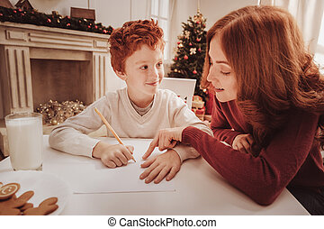 Close up of careful mother helping her child with drawing