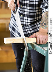 Close-up of carpenter sawing wood with hand saw