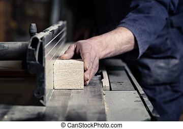 Close up of Carpenter's hands cutting wood with tablesaw in workshop; selective focus