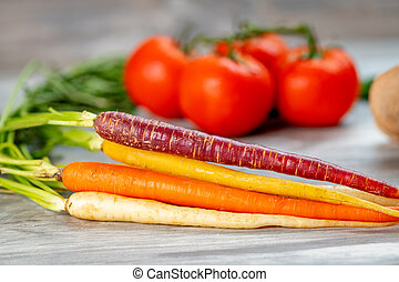 Close up of carrots along with other vegetables in the background
