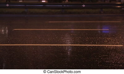 Close up of cars and rain on wet pavement at night.