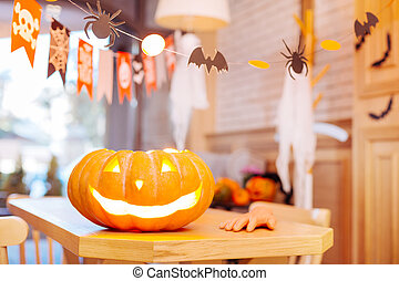 Close up of carved Halloween pumpkin with candle inside standing on table