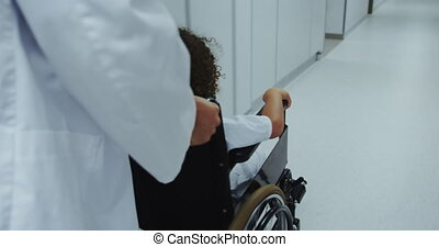 Close-up of Caucasian male doctor pushing pushing African american boy in wheelchair in hospital 4k