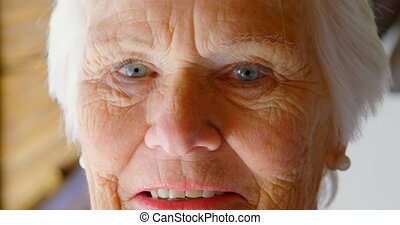 Close-up of Caucasian senior woman looking at camera in a comfortable home 4k