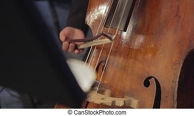 Close-up of cellist hand playing cello with bow.