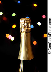 Close up of champagne bottle against bokeh Christmas lights on black background for Happy New Year text or message.