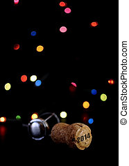 Close up of champagne cork with Happy New Year message, 2014, against black background with Christmas lights bokeh.