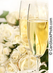 Close-up of champagne glasses with a bouquet of roses