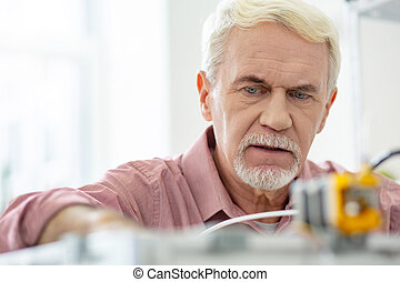 Close up of charming senior man working with 3D printer