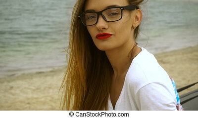young girl with red lips wears a sunglasses and take a lollipop to her mouth