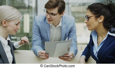Close-up of cheerful businessman talking and discussing about financial report with business female colleagues sitting on sofa in meeting room