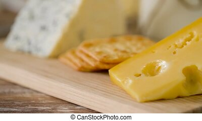 close up of cheese and cracker on wooden board - food and...
