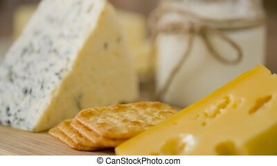 close up of cheese, crackers and butter on table - food and...