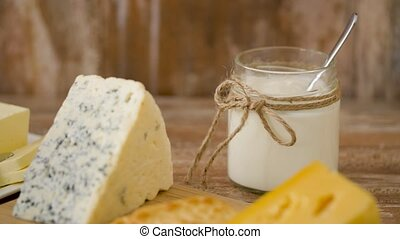 close up of cheese, yogurt and butter on table - food and...