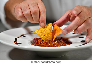 Close up of chef hands adding some nachos to a chili dish on a table. Exotic food and cooking concept.