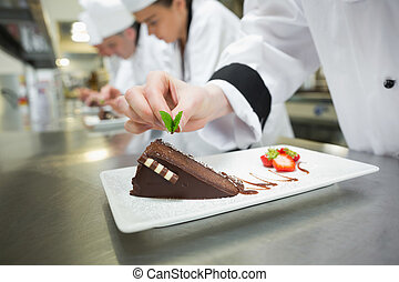 Close up of chef putting mint leaf on chocolate cake in busy...