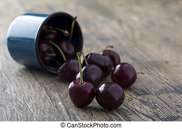 Close-up of cherries in a blue cup on brown background