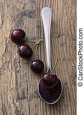 Close-up of cherries in a silver spoon on brown background
