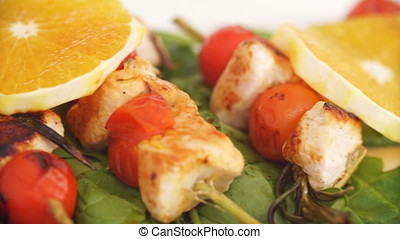 Close up of chicken kebabs served with tomato cherry and...