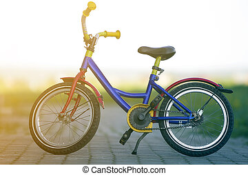 Close-up of child bright multicolored blue, yellow and red bicycle left supported on side stand in middle of empty paved street on blurred bright bokeh background. Children active lifestyle concept.