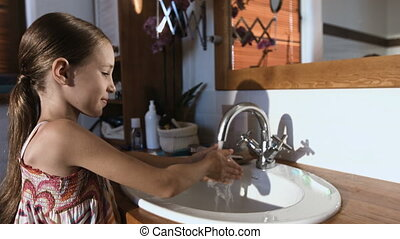 Close-up of child girl cleaning teeth with toothbrush in the bathroom.