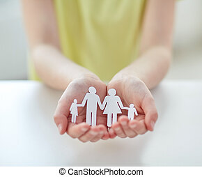 close up of child hands with paper family cutout