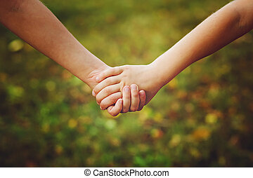 Close up of children holding his hand in summer park outdoor.