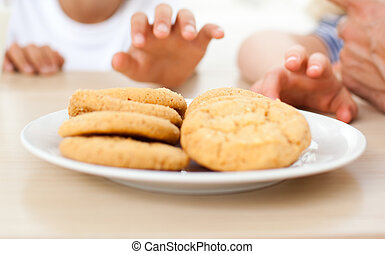 Close-up of children taking biscuits