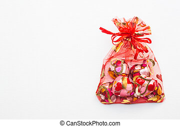 Chocolate heart-shaped in red bag on white background