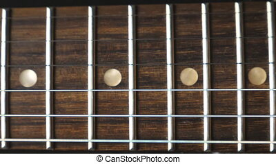 Close up of chords being strummed and vibrating during playing. Trembling guitar strings against fret. Beautiful background with wooden texture. Music performance. Slow motion.