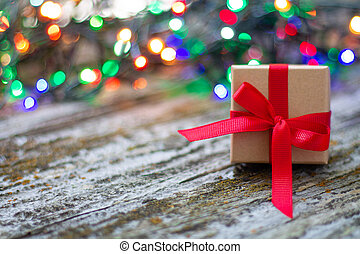 Close-up of christmas gift box with red ribbon on wooden rustic table with colorful bokeh background
