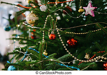Close-up of Christmas tree decorations, garlands and beads on the branches of a Christmas tree.