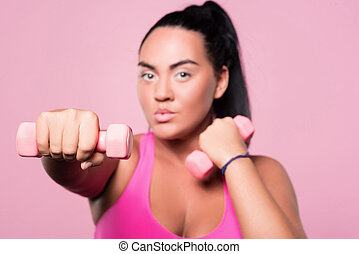 Close up of chubby woman doing boxing exercises with dumbbells