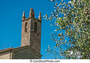 Close-up of church and bell tower with trees around in the hamlet of Monteriggioni.