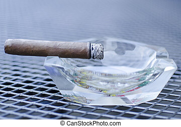 Close up of cigar with glass ashtray on the wired table