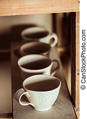 Close up of clay cups placed on wooden plank