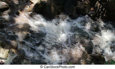 Close-up of clear water flowing through pebbles in summer,...