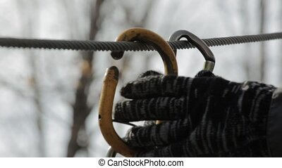close-up of climbing carbine on high ropes course in extreme...