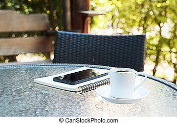 close up of coffee cup and notebook wtih smartphone on coffee cafe