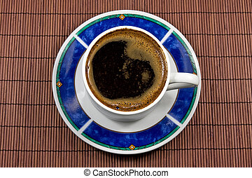 coffee cup on bamboo tablecloth
