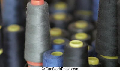 CLose up of coils with colored threads. Bobbins are stacked...
