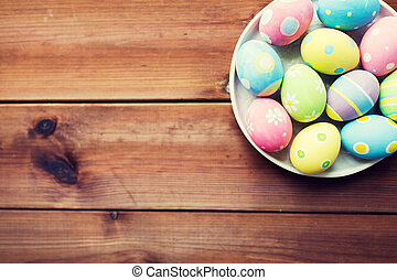 close up of colored easter eggs on plate - easter, holidays,...